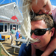 "9/7/09 - HARPSWELL, Maine --  Ava Saxton, 5, rides on her father, Billy's, shoulders outside of Dolphin Marina, which her father and Uncle Chris have taken over from her grandparents.  The young entrepreneurs plan on making changes to the family-run property in the coming months. They will increase the size of the restaurant, adding tables -- but keeping the ""charm"" of the location. They also plan on increasing to over 100 moorings in the bay.  Photo by Roger S. Duncan"