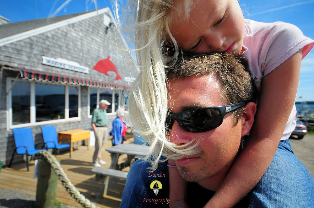 """9/7/09 - HARPSWELL, Maine --  Ava Saxton, 5, rides on her father, Billy's, shoulders outside of Dolphin Marina, which her father and Uncle Chris have taken over from her grandparents.  The young entrepreneurs plan on making changes to the family-run property in the coming months. They will increase the size of the restaurant, adding tables -- but keeping the """"charm"""" of the location. They also plan on increasing to over 100 moorings in the bay.  Photo by Roger S. Duncan"""