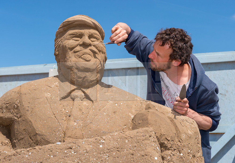 """© Licensed to London News Pictures. 12/05/2019. Weston-super-Mare, North Somerset, UK. The Weston-super-Mare Sand Sculpture Festival at Weston's beach. A Brexit related sand sculpture """"Off With My Head"""" is worked on by Dutch artist JOHANNES HOGEBRINK (pictured). The sculpture depicts a large globe and in the centre of it is Theresa May putting her head under a falling guillotine, with Vladimir Putin and Donald Trump watching the spectacle of Brexit. The piece stands 4m tall and 6m wide and will take a total of 8 days to complete. The Weston Sand Sculpture Festival promises a new theme each year and this year the broad """"What If…?"""" topic has allowed artists to create conceptual pieces of art portraying some important and alarming messages from Climate Change to Feminism. Photo credit: Simon Chapman/LNP"""