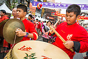 """10 FEBRUARY 2013 - BANGKOK, THAILAND: A band accompanying a Lion Dance troupe marches down Yaowarat Road on Chinese New Year in the Chinatown section of Bangkok. Bangkok has a large Chinese emigrant population, most of whom settled in Thailand in the 18th and 19th centuries. Chinese, or Lunar, New Year is celebrated with fireworks and parades in Chinese communities throughout Thailand. The coming year will be the """"Year of the Snake"""" in the Chinese zodiac.    PHOTO BY JACK KURTZ"""