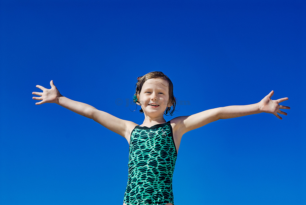 Joyous girl in bathing suit and open arms at the beach.