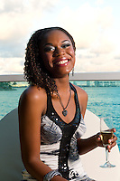 Young african american enjoys a glass of champagne in a terrace with ocean view.