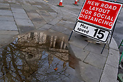 The reflection of St Paul's Cathedral is seen in a puddle on the pavement, alongside a traffic sign that warns drivers of a narrowing of the road, widened for social distancing pedestrians during the third lockdown of the Coronavirus pandemic, in the 'City of London', the capital's financial district, aka The Square Mile, on 2nd February 2021, in London, England.