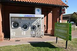Launderette outside Budgens, Holt, Norfolk, UK
