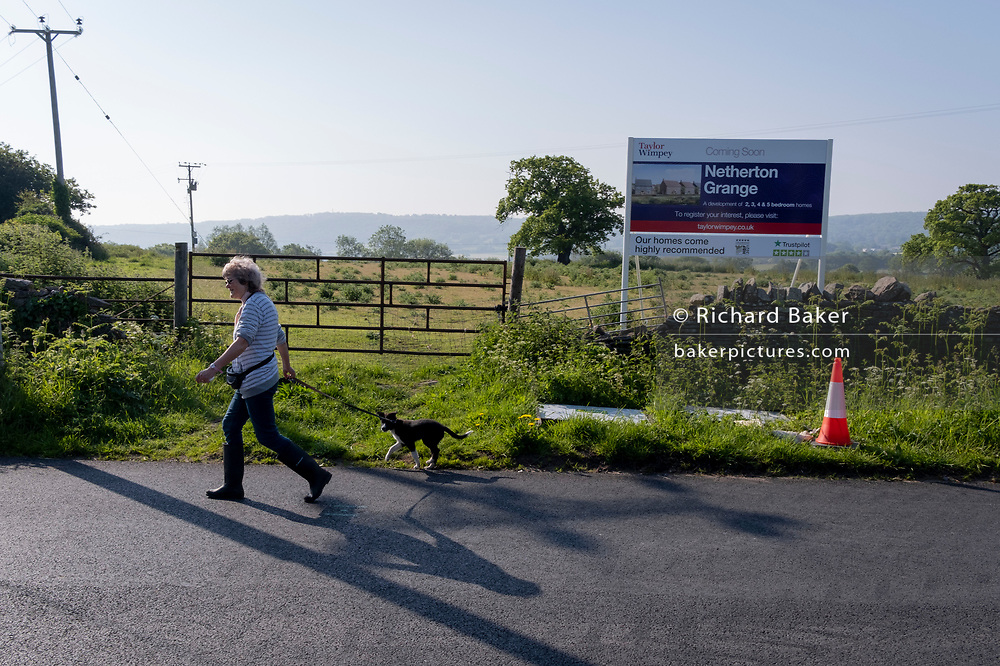 A local dog walker passes an idyllic landscape of green fields and farmland that will soon change forever when it will be built upon by housing developer Taylor Wimpey at Netherton Grange, Youngwood Lane, Nailsea, on 31st May 2021, in Nailsea, North Somerset, England. Nearly 170 homes are set to be built here on the edge of Nailsea after detailed plans were approved. Thirty per cent of the homes will be affordable.