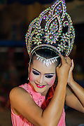 22 NOVEMBER 2013 - BANGKOK, THAILAND: A performer with the Prathom Bunteung Silp mor lam troupe  puts on her costume before a show in Bangkok. Mor Lam is a traditional Lao form of song in Laos and Isan (northeast Thailand). It is sometimes compared to American country music, song usually revolve around unrequited love, mor lam and the complexities of rural life. Mor Lam shows are an important part of festivals and fairs in rural Thailand. Mor lam has become very popular in Isan migrant communities in Bangkok. Once performed by bands and singers, live performances are now spectacles, involving several singers, a dance troupe and comedians. The dancers (or hang khreuang) in particular often wear fancy costumes, and singers go through several costume changes in the course of a performance. Prathom Bunteung Silp is one of the best known Mor Lam troupes in Thailand with more than 250 performers and a total crew of almost 300 people. The troupe has been performing for more 55 years. It forms every August and performs through June then breaks for the rainy season.     PHOTO BY JACK KURTZ