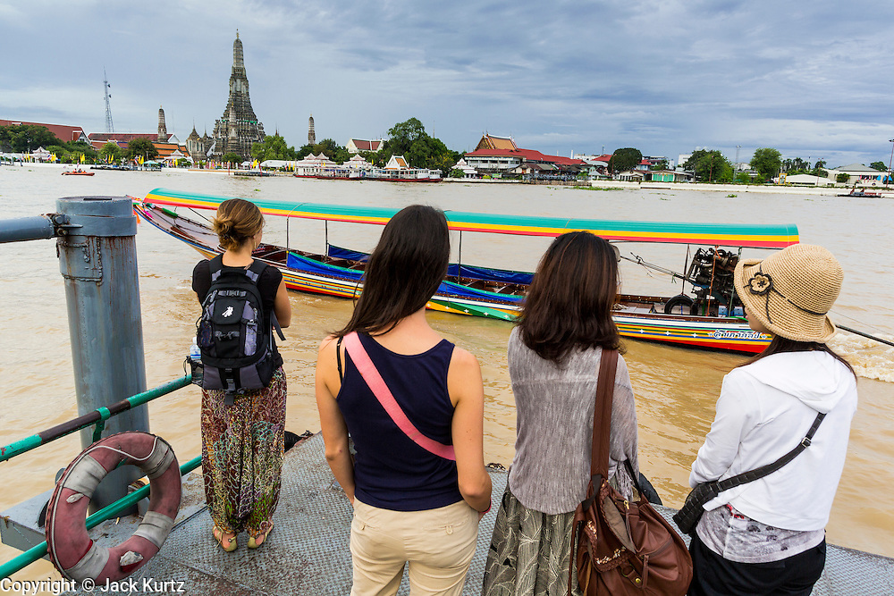 "23 SEPTEMBER 2013 - BANGKOK, THAILAND:  Tourists wait to catch a ferry to take them across the Chao Phraya River in Bangkok to Wat Arun on the last day the world famous stupa at the temple is open to the public. The full name of the temple is Wat Arunratchawararam Ratchaworamahavihara. The outstanding feature of Wat Arun is its central prang (Khmer-style tower). The world-famous stupa, known locally as Phra Prang Wat Arun, will be closed for three years to undergo repairs and renovation along with other structures in the temple compound. This will be the biggest repair and renovation work on the stupa in the last 14 years. In the past, even while large-scale work was being done, the stupa used to remain open to tourists. It may be named ""Temple of the Dawn"" because the first light of morning reflects off the surface of the temple with a pearly iridescence. The height is reported by different sources as between 66,80 meters and 86 meters. The corners are marked by 4 smaller satellite prangs. The temple was built in the days of Thailand's ancient capital of Ayutthaya and originally known as Wat Makok (The Olive Temple). King Rama IV gave the temple the present name Wat Arunratchawararam. Wat Arun officially ordained its first westerner, an American, in 2005. The central prang symbolizes Mount Meru of the Indian cosmology. The temple's distinctive silhouette is the logo of the Tourism Authority of Thailand.          PHOTO BY JACK KURTZ"