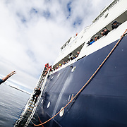 Passengers take the polar plunge, diving into the freezing waters from the side of the ship near Melchior Island on the western coast of the Antarctic Peninsula. The Polar Pioneer is a Russian ice-strengthened ship operated by Australian company Aurora Expeditions.
