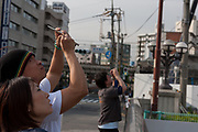 People take photos with mobile phones of Tokyo Sky Tree under construction. Tokyo, Japan. Monday June 21st 2010. In this image the unfinished telecommunication tower stands at 398 metres high, Upon completion it will measure 634 metres from top to bottom, becoming the tallest structure in East Asia.