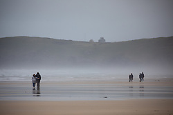 © Licensed to London News Pictures. 04/07/2020. Perranporth, UK. Members of the public enjoy Perranporth beach in Cornwall today, despite wet weather. Today marks a lift in COVID-19 restrictions, as pubs are allowed to open, whilst customers must still follow social distancing guidelines. Tens of thousands of tourists are due to arrive in Cornwall over this weekend, as overnight stays within England are also allowed. Photo credit : Tom Nicholson/LNP