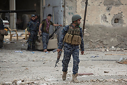 Licensed to London News Pictures. 01/04/2017. Mosul, Iraq. An Iraqi Federal Police officer looks for ISIS snipers as he crosses a road in West Mosul, Iraq, today (01/04/2017). Iraqi forces continue to fight house to house as they push further into West Mosul. Iraqi forces are now advancing on the city's old districts where Islamic State fighters still hold out. Photo credit: Matt Cetti-Roberts/LNP