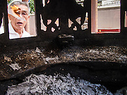 """26 AUGUST 2013 - BANGKOK, THAILAND:     A man burns the receipt he received after donating a coffin to the Poh Teck Tung Foundation for Hungry Ghost Month in Bangkok. Burning the receipt, which is a form of Ghost Money, is a part of the ritual of donating coffins. Poh Teck Tung operates hospitals and schools and provides assistance to the poor in Thailand. The seventh lunar month (August - September in 2013) is when the Chinese community believes that hell's gate will open to allow spirits to roam freely in the human world for a month. Many households and temples will hold prayer ceremonies throughout the month-long Hungry Ghost Festival (Phor Thor) to appease the spirits. During the festival, believers will also worship the Tai Su Yeah (King of Hades) in the form of paper effigies which will be """"sent back"""" to hell after the effigies are burnt.   PHOTO BY JACK KURTZ"""