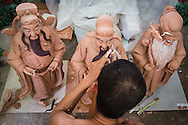 Top view of a Vietnamese man shaping a clay statuette in Bat Trang ceramic village, Hanoi outskirts, Vietnam, Southeast Asia