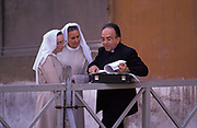 A Catholic priest leans his briefcase on railings to show a document to two nuns in St. Peter's Square, on 3rd November 1999, in Vatican City, Rome, Italy.