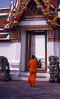 A young monk approaches an archway in Wat Pho, Bangkok.