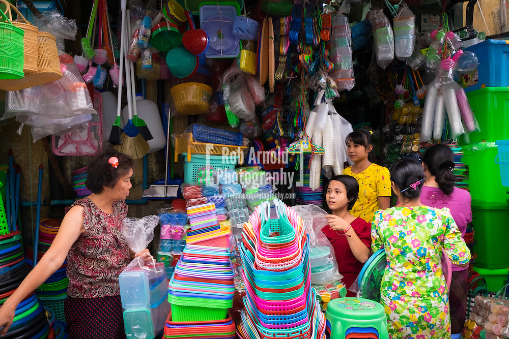 Women and girls selling plastic goods on a stall in a street market in Downtown Yangon.