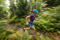 Female trail runner (Katy Farber) speeds along a forest trail in the green mountains of Vermont.  Trail on Putnam State Forest, White Rocks/Hunger Mtn. Patterson Brook Project