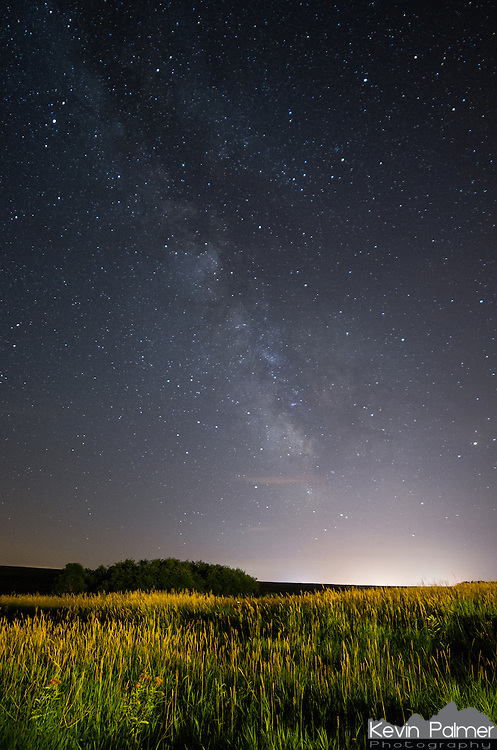 The milky way hangs in the sky above Blue Mounds State Park in Minnesota. The light pollution along the horizon is from the small town of Luverne.