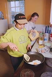 Two residents preparing breakfast in communal kitchen of women only homeless hostel,