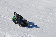 Boy of 7 slides down the snowy slopes on a sleigh view from front