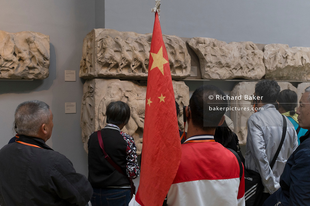 A Chinese tour group listen to historical commentary about the Parthenon (Elgin) Marbles in the British Museum, on 12th June 2018, in London, England.