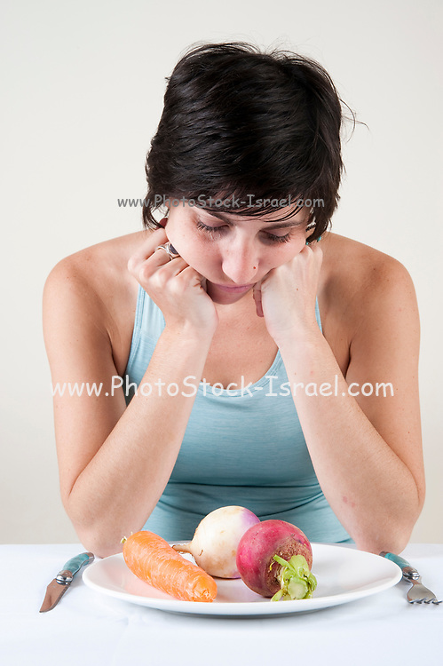 Eating Disorder concept - Studio shot of a hungry depressed and frustrated female model in her 20s with a plate of vegetables in front of her on white background