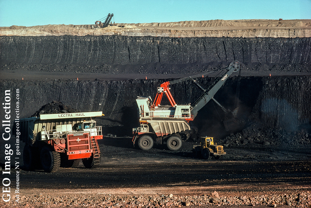A seventy-foot coal seam is stripped by a huge machine.