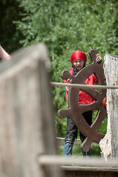 Girl pretending as pirate holding ship rudder in playground, Bavaria, Germany