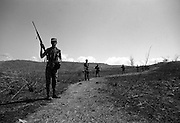 Government forces on patrol through burnt hill country, El Salvador.