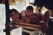 1989: Penan native woman and her child, families of Along Sega and Awing Banai,  in sulap structure made from bamboo, wood and rattan. Long Tedang, Limbang district, Sarawak, Borneo <br /> <br /> Tropical rainforest and one of the world's richest, oldest eco-systems, flora and fauna, under threat from development, logging and deforestation. Home to indigenous Dayak native tribal peoples, farming by slash and burn cultivation, fishing and hunting wild boar. Home to the Penan, traditional nomadic hunter-gatherers, of whom only one thousand survive, eating roots, and hunting wild animals with blowpipes. Animists, Christians, they still practice traditional medicine from herbs and plants. Native people have mounted protests and blockades against logging concessions, many have been arrested and imprisoned.