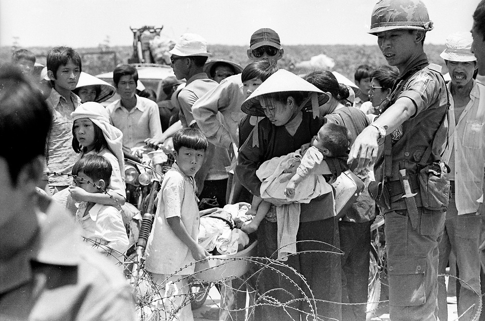 South Vietnamese refugees fleeing from Xuan Loc seen at a road block as they desperately try to get to safety as the battle rages before the city falls to the North Vietnamese. April 1975. Photograph by Terry Fincher