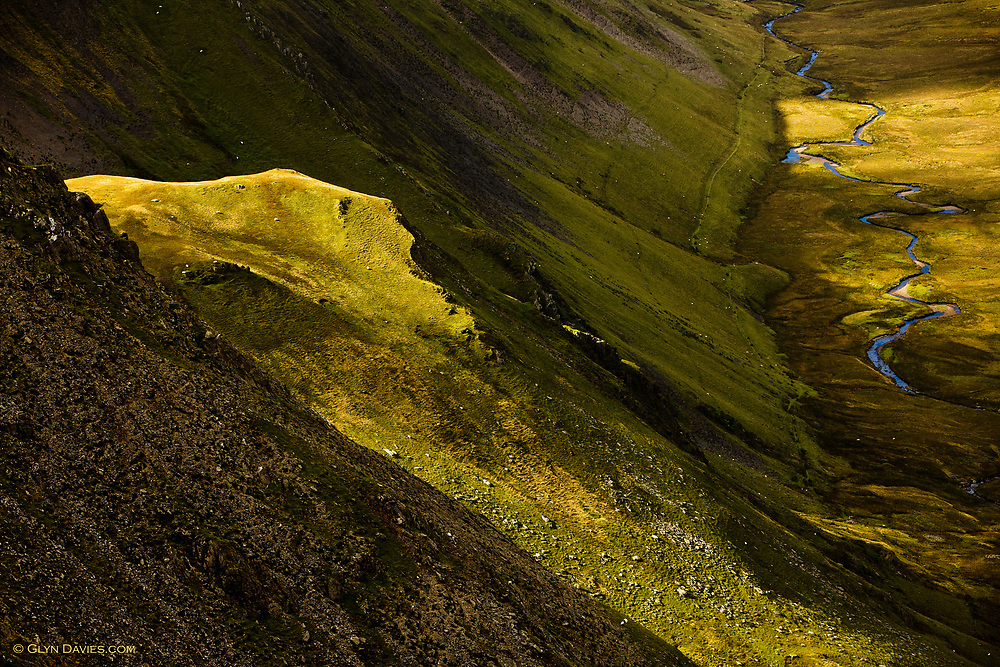 A face screams from the side of Carnedd Dafydd as sunlight creeps over the top of a higher col. This high mountain river here in Cwm Llachar runs down to the town of Bethesda before exiting at the Menai Strait near Bangor.