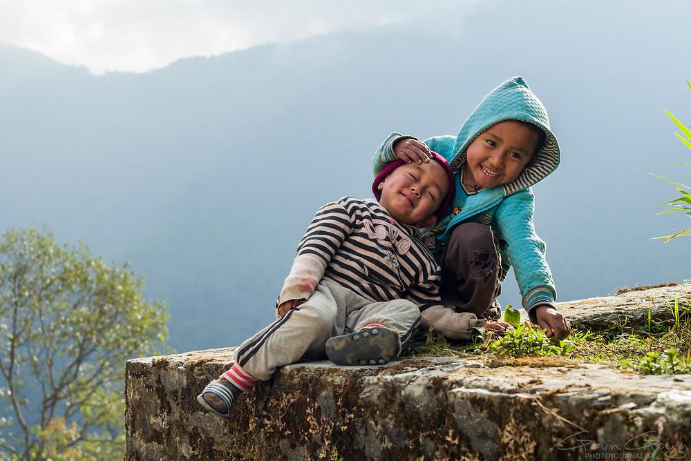 Two young boys laughing and playing beside a trekking path in the Annapurna region, Ghandruk to Birethanti Trek Path, Ghandruk, Nepal