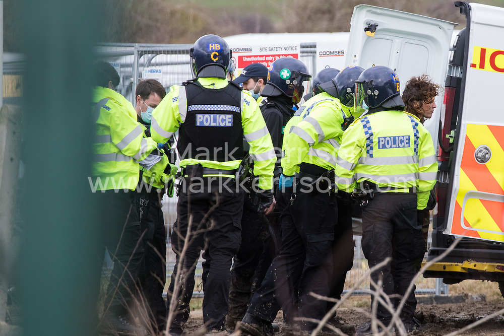 Steeple Claydon, UK. 24 February, 2021. Thames Valley Police officers arrest an activist during an operation to evict activists opposed to the HS2 high-speed rail link from ancient woodland known as Poors Piece. Thames Valley Police stepped in to replace National Eviction Team bailiffs. The activists created the Poors Piece Conservation Project in the woodland in spring 2020 after having been invited to stay on the land by its owner, farmer Clive Higgins.