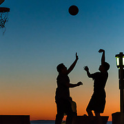 Two friends play a game of one on one during sunset at the basketball courts of Main Beach Park in Laguna Beach, California.  ©Michael Der Photography/ALL RIGHTS RESERVED.<br />