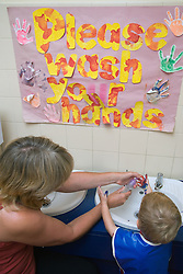 Nursery teacher and boy washing hands after painting at an early start unit ran by the Nottingham Royal Society for the Blind (NRSB),