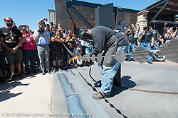 Kendall Polster cuts the Harley-Davidson logo adorned chain he fabricated for the official chain cutting ceremony at the brand new Harley-Davidson Rally Point on the corner of Main Street and Harley Way during the 75th Annual Sturgis Black Hills Motorcycle Rally.  SD, USA.  July 31, 2015.  Photography ©2015 Michael Lichter.