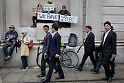 Asian businessmen look at environmental activists protesting about Climate Change during the blockade outside the Bank of England in the heart of the capitals financial district, the City of London aka the Square Mile, on the seventh day of a two-week prolonged worldwide protest by members of Extinction Rebellion, on 14th October 2019, in London, England.