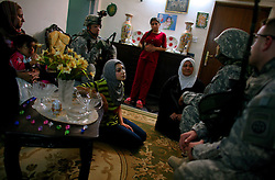 Paratroopers with Bravo Battery 2-319 2BCT 82nd Airborne Division question a family of Shia women whose father and husbands have been forced into exile in Syria after receiving repeated death threats from Sunni insurgents in their mixed neighborhood on Monday April 23, 2007.