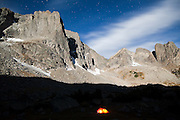 Moonlight illuminates Warrior Peak above a glowing tent in the Cirque of the Towers, Popo Agie Wilderness, Wind River Range, Wyoming.