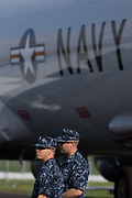 US Navy personnel guarding a Poseidon jet aircraft, exhibited at the Farnborough Air Show, England. The two men in uniform stand below the large US Navy lettering on the patrol and surveillance jet's fuselage. The Boeing P-8 Poseidon (formerly the Multimission Maritime Aircraft or MMA) is a military aircraft developed for the United States Navy (USN). It conducts anti-submarine warfare (ASW), anti-surface warfare (ASUW), and shipping interdiction, along with an electronic signals intelligence (ELINT) role. This involves carrying torpedoes, depth charges, SLAM-ER missiles, Harpoon anti-ship missiles, and other weapons.