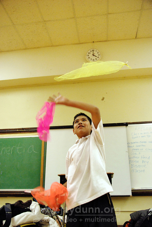 """USA, Chicago, IL, December 12, 2009.  Miguel Avalos displays good form as he practices juggling scarves. Students in the """"At-Risk After School Program"""" at Maria Saucedo Scholastic Academy receive training in basic physics principles through an innovative new program called """"Circus Galactica"""" put on by Pros Arts, a non-profit organization founded in 1978 by professional artists dedicated to the Pilsen/Little Village communities. In a residency that directly integrates science and art, veteran circus performers Douglas Grew and Paul Lopez bring the importance of """"balance, focus and presentation"""" into hands-on lessons about gravity, inertia, and the dynamics of objects in motion. Photo for Hoy by Jay Dunn."""
