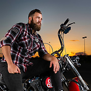 """Adam Gilbert, drummer of the band Starset, poses next to """"Fever"""" his 2010 Harley-Davidson Softail Deluxe motorcycle. Photo by Leonardo Carrizo"""