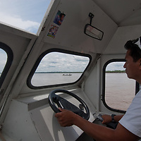 A Peruvian Indian drives a passenger boat up the Amazon River near Iquitos.