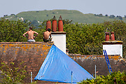 Two male roofers sit on a house roof top during a break on the 21st of July 2021 in Folkestone, Kent, United Kingdom. Roofing is one of the most dangerous professions, some roofers in the UK still work without the correct safety equipment.