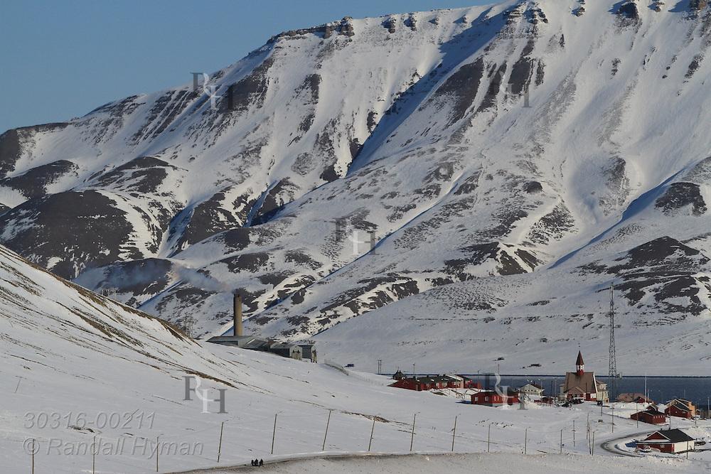 Snowy mountains loom behind town of Longyearbyen in April; Svalbard, Norway.