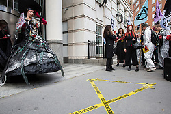 London, UK. 2 July, 2019. Climate change activists from Extinction Rebellion Art and Culture protest outside the offices of Eni S.p.A. during a silent procession visiting the offices of five major oil companies - ENI, CNPC, Saudi Aramco, Repsol and BP - to declare them a crime scene.