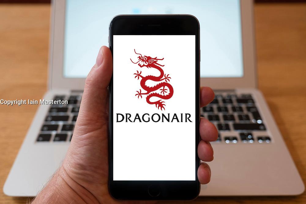 Using iPhone smartphone to display logo of Dragonair airline from Hong Kong