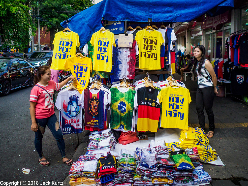 """03 JULY 2018 - BANGKOK, THAILAND: Venders in Bobae Market, a clothing market in Bangkok, sell World Cup tee shirts and yellow tee shirts that say """"Long Live the King"""" in advance of the Thai King's birthday. The birthday of King Maha Vajiralongkorn Bodindradebayavarangkun, Rama X, is 28 July. The King, the only son of Thailand's late King Bhumibol Adulyadej, became the King of Thailand in 2016 after the death of his father. King Vajiralongkorn was born on 28 July 1952, a Monday. In Thai culture each day of the week has a color, and yellow is the color is associated with Monday, so people wear yellow for the month before his birthday to honor His Majesty.   PHOTO BY JACK KURTZ"""