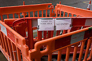 Permit to Work and No Entry notices in construction barriers, in a south London street. Looking down at this detail view of the street barriers, ordinarily designed for roadworks and pedestrian health and safety barriers, we see the temporary paper attached to the interlocking plastic items warning us pedestrians of entering a restricted area. It is of course pointless and indicative of bylaws and safety concerns gone mad. They have apparently been stacked until needed for further use during roadworks for London's cycling superhighway.
